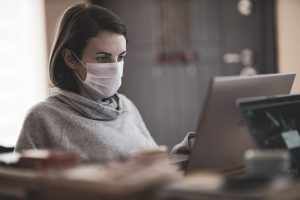 Woman wearing mask working on laptop